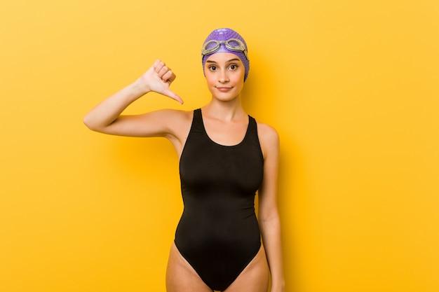 Młodej pływaczki caucasian kobieta pokazuje niechęć gest, kciuki zestrzela