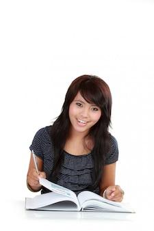 Młodej powabnej kobiety czytelnicza książka odizolowywająca na bielu