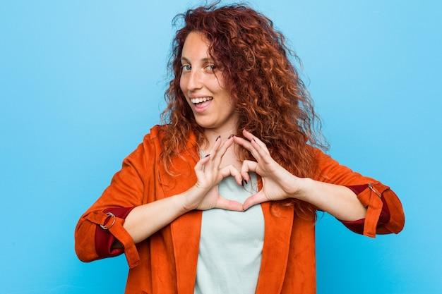 Młodej rudzielec elegancka kobieta uśmiecha się kierowego kształt z rękami i pokazuje