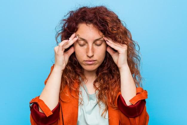 Młodej rudzielec eleganckiej kobiety wzruszające świątynie i mieć ból głowy.