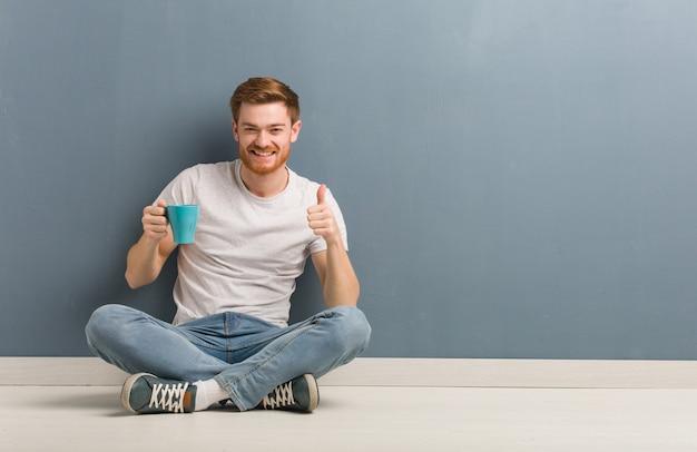 Młodej rudzielec mężczyzna studencki obsiadanie na podłoga uśmiecha się kciuk up i podnosi. on trzyma kubek kawy.