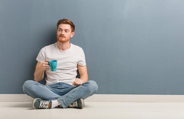 Młodej rudzielec studencki mężczyzna obsiadanie na podłoga ono uśmiecha się ufny i krzyżuje ręki, przyglądający up. on trzyma kubek kawy.