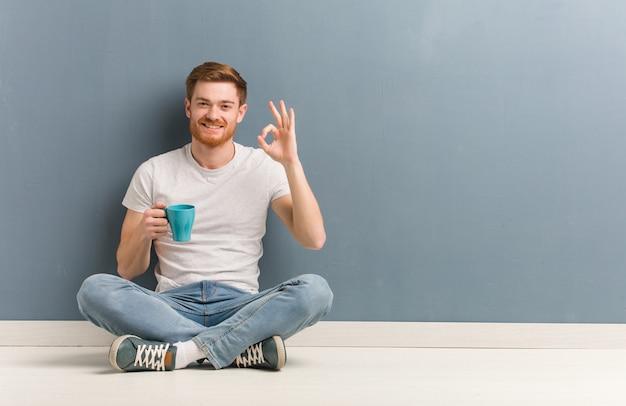 Młodej rudzielec studencki mężczyzna obsiadanie na podłoga rozochocony i ufny robi ok gestowi. on trzyma kubek kawy.
