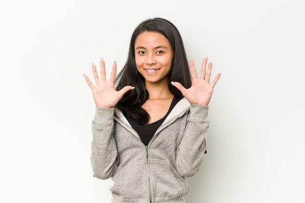 Młodej sprawności fizycznej chińska kobieta pokazuje liczbę dziesięć z rękami.