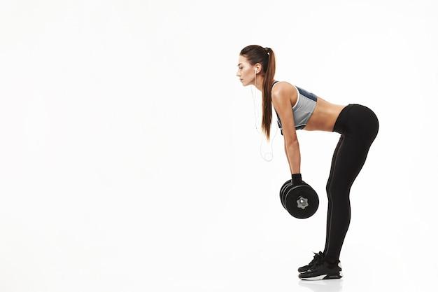 Młodej sprawności fizycznej sporty kobieta trenuje mień dumbbells na bielu w hełmofonach.