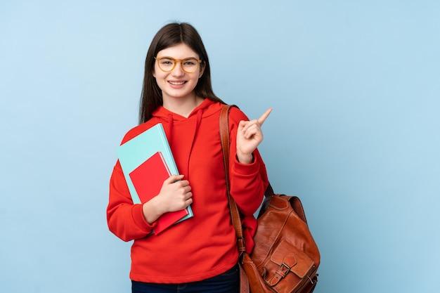 Młodej ukraińskiej nastolatki studencka dziewczyna trzyma sałatkę nad odosobnionym błękitnym ściennym wskazuje palcem strona