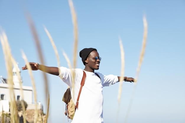 Młodość, szczęście, wolność i podróże. wesoły młody afroamerykanin podróżnik w kapeluszu i okularach przeciwsłonecznych, rozkładający ramiona i uśmiechający się radośnie, czując się zrelaksowany i w harmonii z naturą