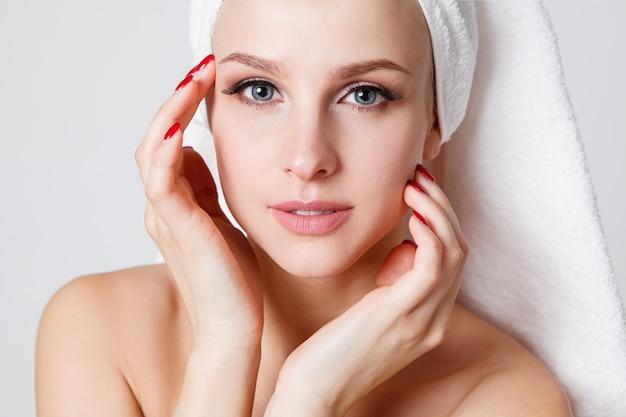 Młodości kobiety z ręcznikiem na jej głowie patrzeje kamerę. wnętrz. ochrona skóry
