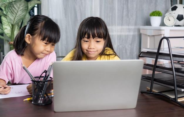 Młodsza i starsza siostra uczy się i uczy online w domu, koncepcja edukacji i wiedzy