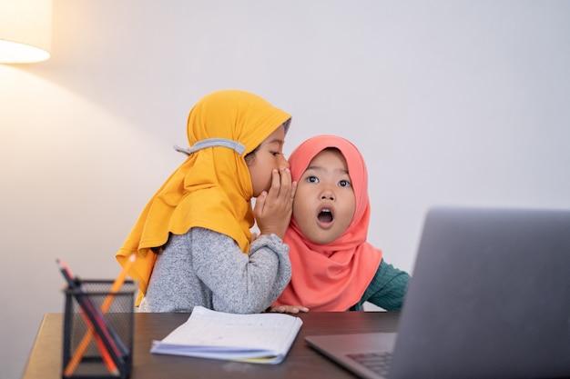 Młodsza siostra szepcze coś do swojego rodzeństwa i jest w szoku podczas korzystania z laptopa w domu