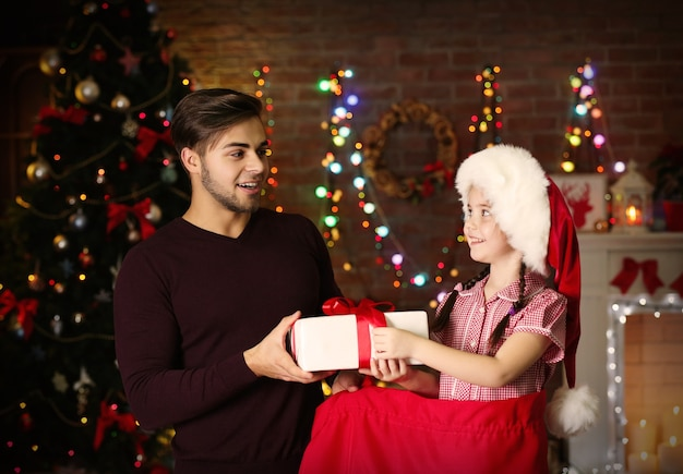 Młodsza siostra w worku świętego mikołaja daje prezent swojemu starszemu bratu na tle bożego narodzenia
