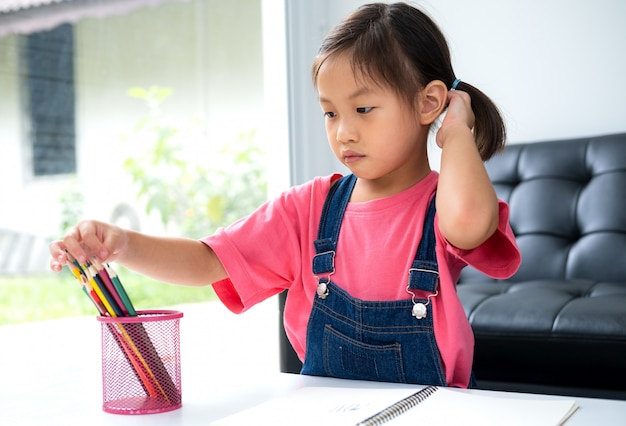 Młodsze dziecko azjatyckie uczy się i uznaje w domu