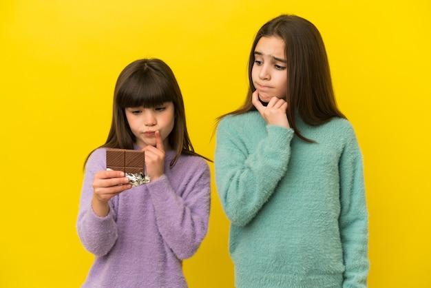 Młodsze siostry odosobnione biorąc czekoladową tabliczkę i mając wątpliwości