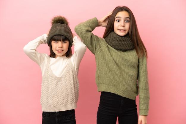 Młodsze siostry ubrane w zimowe ubrania na białym tle biorą ręce za głowę z powodu migreny