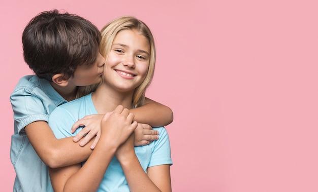 Młodszy brat całuje siostrę w policzek