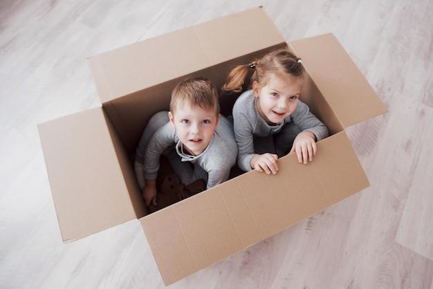 Młodszy brat i dziecko siostra bawić się w kartonowych pudełkach w pepinierze