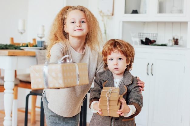 Młodszy brat i siostra dają prezenty, stonowana fotografia