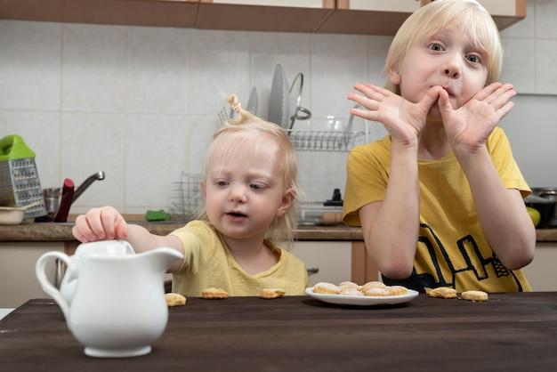Młodszy brat i siostra jedzą śniadanie w kuchni