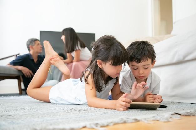 Młodszy brat i siostra leżą na podłodze w salonie i używają cyfrowych gadżetów z aplikacjami do nauki, gdy rodzice siedzą razem