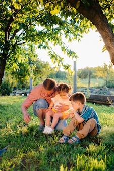 Młodszy brat i siostra sadzą sadzonki ze swoim ojcem w pięknym wiosennym ogrodzie o zachodzie słońca. nowe życie. ratować środowisko. ostrożne podejście do otaczającego świata i przyrody.