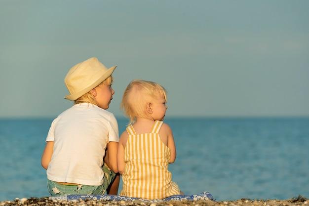 Młodszy brat i siostra siedzą nad brzegiem morza i patrzą w dal