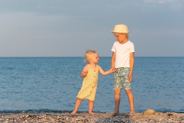 Młodszy brat i siostra trzymają się za ręce i spacerują wzdłuż brzegu morza