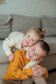Młodszy brat i siostra w przytulnych swetrach z dzianiny bawią się w domu. portret ładny młodszy brat i siostra. spadek.