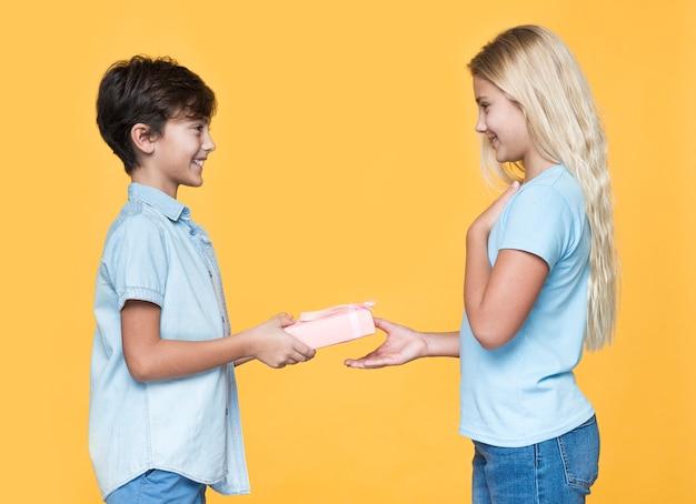 Młodszy brat oferuje prezent siostrze
