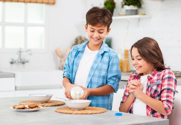 Młodszy brat pomaga siostrze na śniadaniu