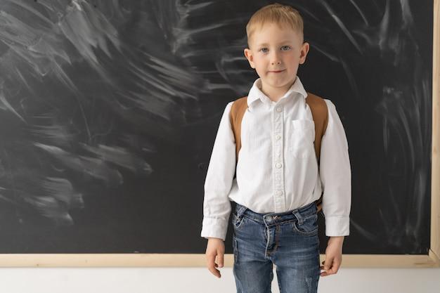 Młodszy uczeń stoi przy tablicy