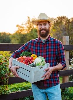 Młody 30-35 lat młody brodaty mężczyzna męski rolnik kapelusz z pudełkiem świeżych ekologicznych warzyw ogród zachód słońca.