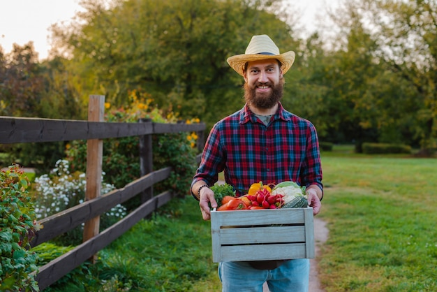 Młody 30-35 lat młody brodaty mężczyzna męski rolnik kapelusz z pudełkiem świeżych warzyw ekologicznych ogród
