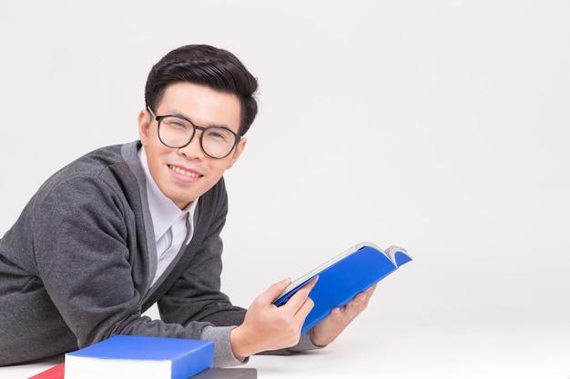 Młody absolwent azji z akcesoriami do nauki.