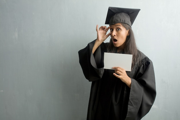 Młody absolwent indyjska kobieta na ścianie zaskoczony i zszokowany