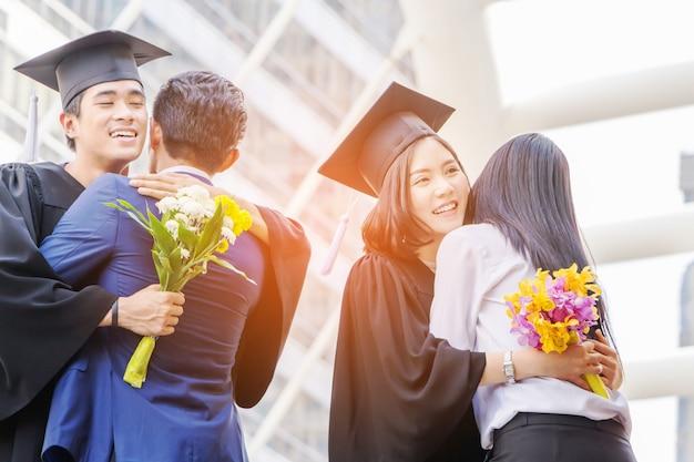 Młody absolwent mężczyzna i kobieta z wycinek ścieżki przytulanie przyjaciela na ukończeniu szkoły