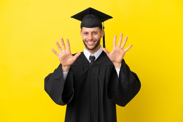 Młody absolwent uniwersytetu kaukaski mężczyzna na białym tle na żółtym tle liczący dziesięć palcami