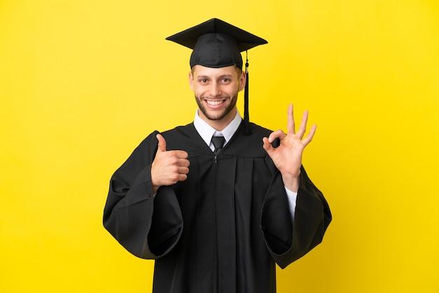 Młody absolwent uniwersytetu kaukaski mężczyzna na białym tle na żółtym tle pokazując znak ok i gest kciuka w górę