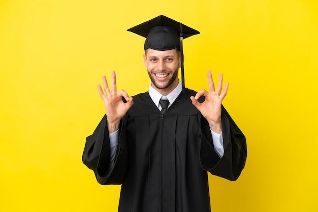 Młody absolwent uniwersytetu kaukaski mężczyzna na białym tle na żółtym tle pokazujący znak ok palcami