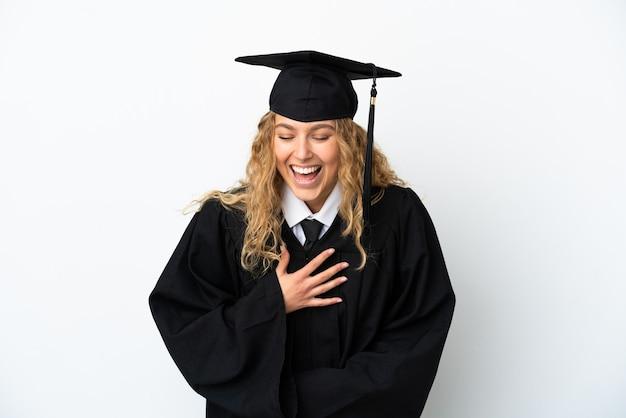 Młody absolwent uniwersytetu na białym tle dużo się uśmiecha