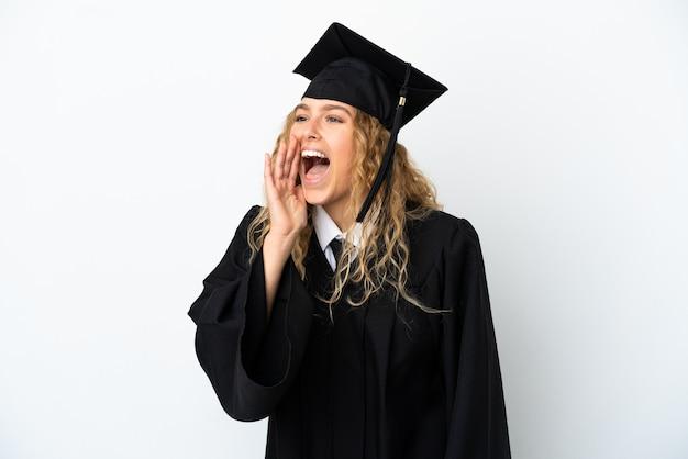 Młody absolwent uniwersytetu na białym tle krzyczy z szeroko otwartymi ustami