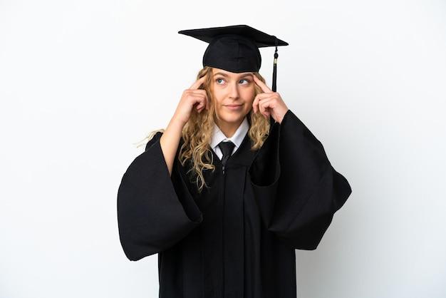 Młody absolwent uniwersytetu na białym tle mający wątpliwości i myślący