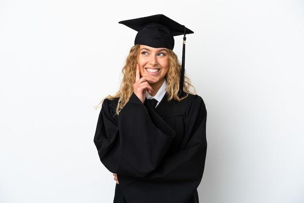 Młody absolwent uniwersytetu na białym tle myślący o pomyśle, patrząc w górę
