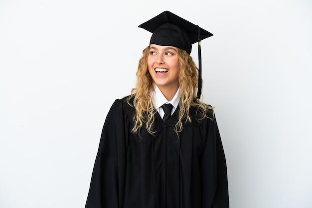 Młody absolwent uniwersytetu na białym tle patrząc w bok i uśmiechnięty