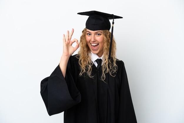 Młody absolwent uniwersytetu na białym tle pokazując znak ok palcami
