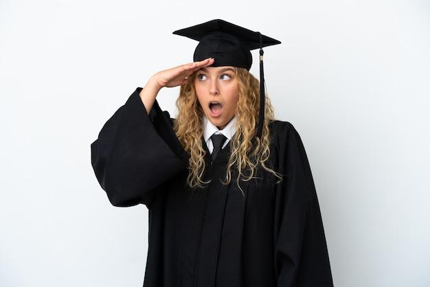 Młody absolwent uniwersytetu na białym tle robi gest zaskoczenia, patrząc w bok