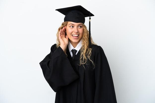 Młody absolwent uniwersytetu na białym tle słuchając czegoś, kładąc rękę na uchu