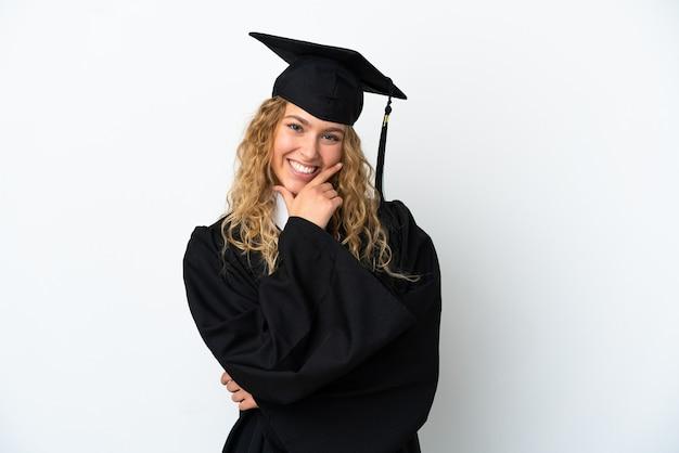 Młody absolwent uniwersytetu na białym tle szczęśliwy i uśmiechnięty