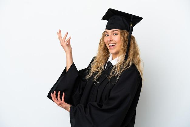 Młody absolwent uniwersytetu na białym tle wyciągając ręce do boku za zaproszenie do przyjścia