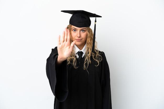 Młody absolwent uniwersytetu na białym tle wykonując gest zatrzymania