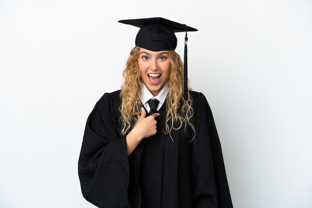Młody absolwent uniwersytetu na białym tle z niespodzianką wyrazem twarzy